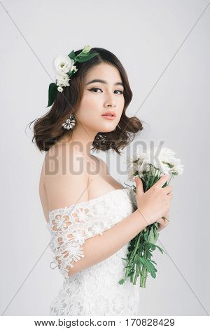 Beautiful asian woman bride on grey background.