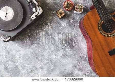 Top view of Vintage Turntable with Guitar and cactus on grunge background Free space for text