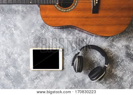 Top view of Guitar with headphone and tablet on grunge background