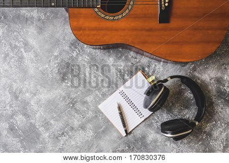 Top view of Guitar with headphonepen and notebook on grunge background