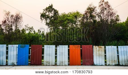 Multicolored colorful galvanized sheets on background trees.