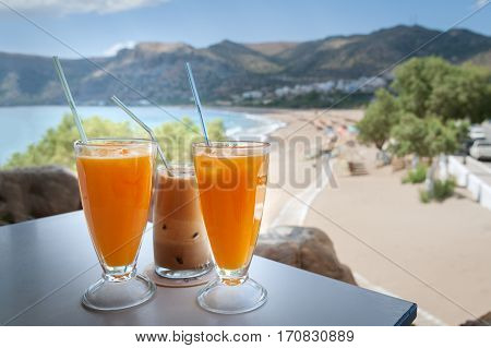 Glasses with orange juice and frappe on a table in the traditional greek tavern.