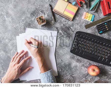 Top view of Male hands writing on paper sheet with Office supplies on Grunge gray background
