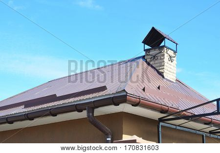 House rain gutter system and roof protection from snow board (Snow guard) on residential house roofing construction with chimney. Metal Roofing Construction.