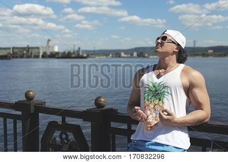 young athletic man stands on the waterfront. river and mountains in the distance.