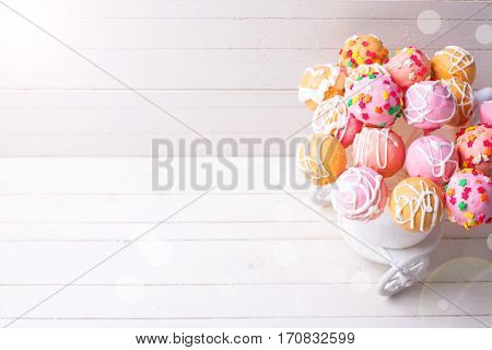 Bright cake pops in ray of light on white wooden background. Selective focus. Place for text.