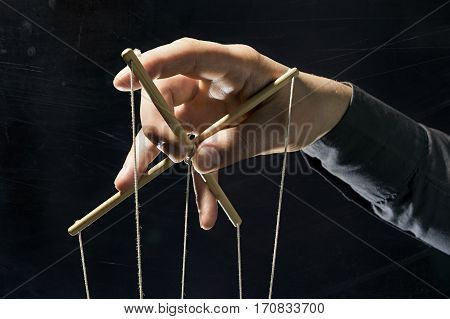 Concept on a theme: the manipulation the dictator dependency slavery etc. Dictator's arm holds strings for manipulation on black background.