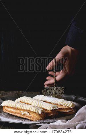 Eclairs On Metal Plate In Woman's Hands