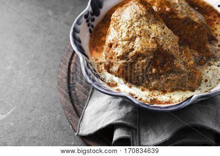 Butter chicken in a bowl with wavy edges on the table horizontal