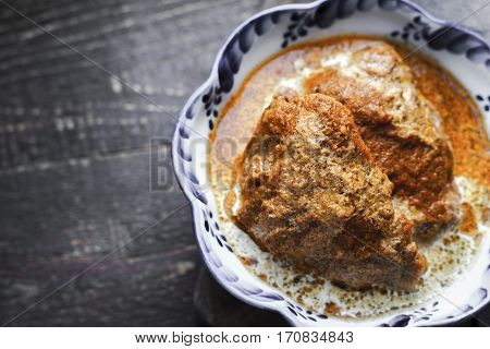 Juicy Butter chicken in a bowl with wavy edges on right horizontal