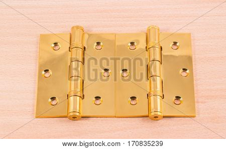 hinges on a wooden background gold color metal