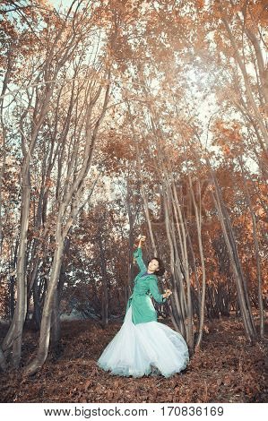 Brunette lady dancing in the autumn forest