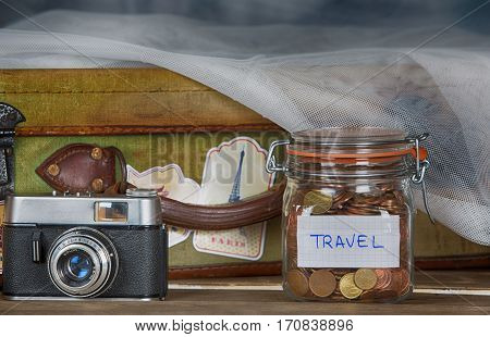 Travel suitcase next to a camera and a piggy bank for travel