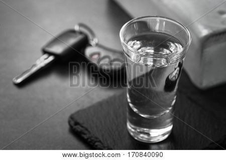 Vodka shot drink and car key. Don't drink and drive concept. Monochrome.