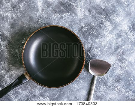 Pan and spade of frying pan on gray grunge background.