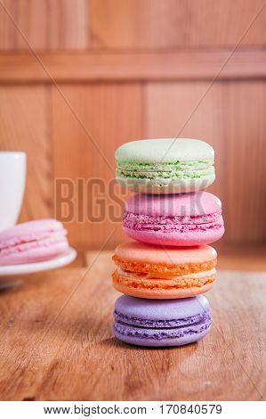 Close Up Of France Dessert Colourfull Macaroons And Cup Of Tea On Wooden Table In Cafe. Selective Fo