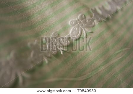 Turquoise textile with white stripes and lace with butterflies