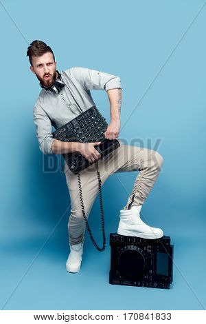 Young trendy male posing with portable mixing console and looking at camera on blue studio background.