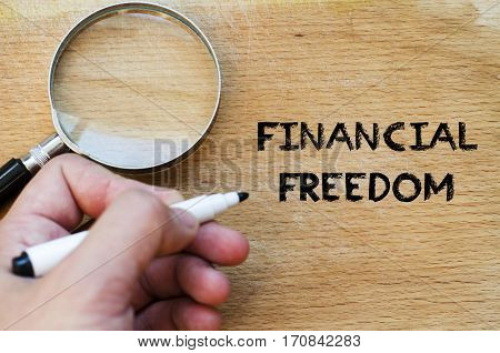 Human hand over wooden background and financial freedom text concept