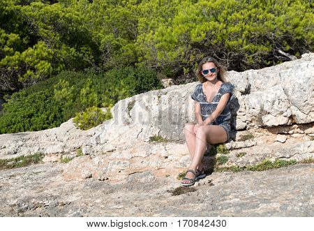 Beautiful girl sits on a rock in a forest Mallorca Spain