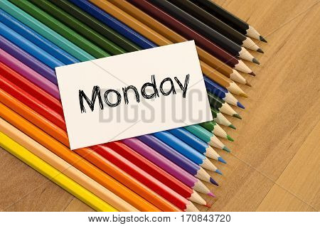 Blank white paper and colored pencils on wooden background