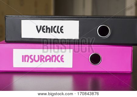 Bright office folders over dark background and vehicle and insurance text concept
