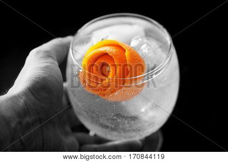 Taking with Hand a Gin Tonic with orange peel rose