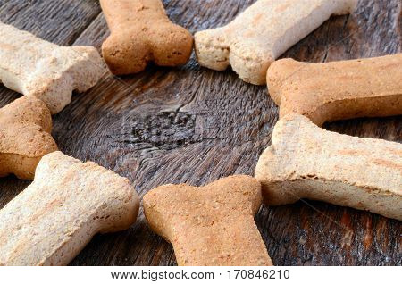 A close up image of several bone shaped dog treats in a circle on a wooden table.