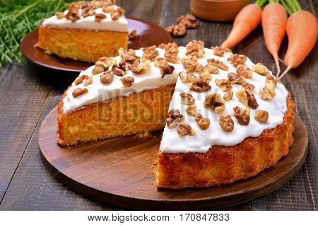 Carrot cake and fresh carrot on wooden table
