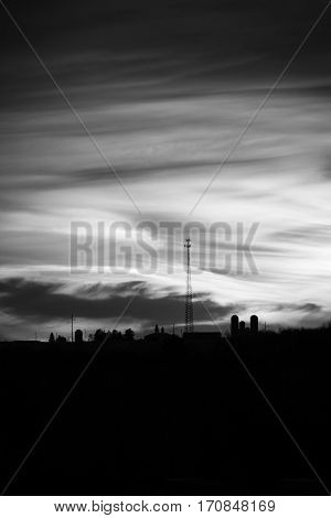 Vertical black and white image of a sunset with a silhouette of farm silos and cell tower.