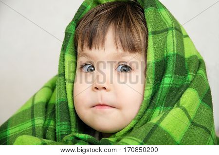 Funny child portrait in blanket warming happy smiling kid face expressing emotion little girl looking at camera warm blanketcomfortable winter concept