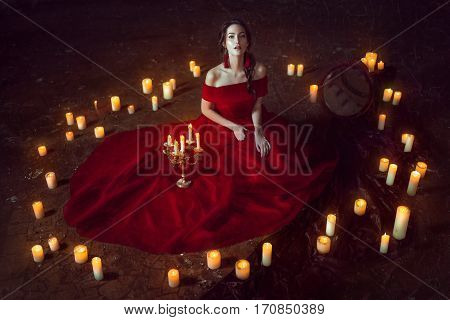 Beautiful lady dressed in red ball gown sitting with candles