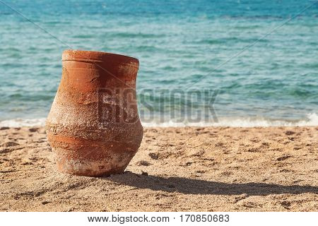 old earthen pitcher standing on the sand near the sea.