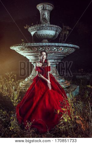 Beautiful lady dressed in red ball gown staying near the fountain