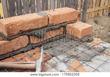Bricklaying Brickwork with Iron Bars Rebar or Reinforcing Steel Bars.