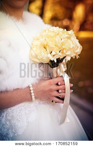 Bride in a white dress is holding a wedding bouquet of roses in hands