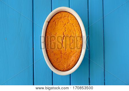 Bright orange pumpkin souffle on blue wooden table overhead view