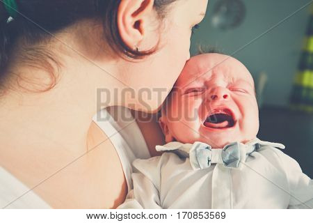 Mother holding crying baby. Young woman with her little son.