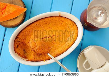 Bright orange pumpkin souffle slice of pfresh pumpkin coffeemaker and coffe cups on blue wooden table overhead view
