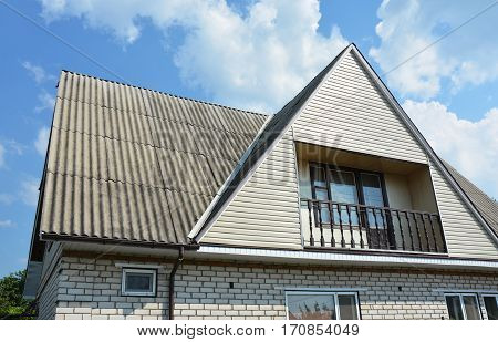 Asbestos roofing construction with gutter system. Gable and Valley type of roof construction.