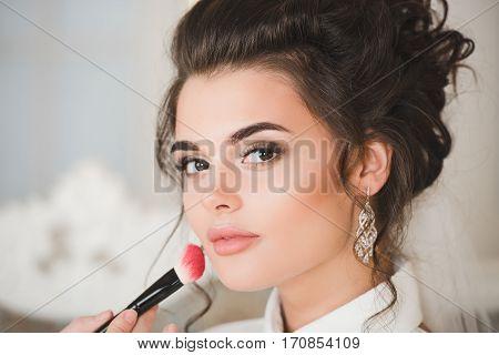 Artist applying blush to wedding make up for bride