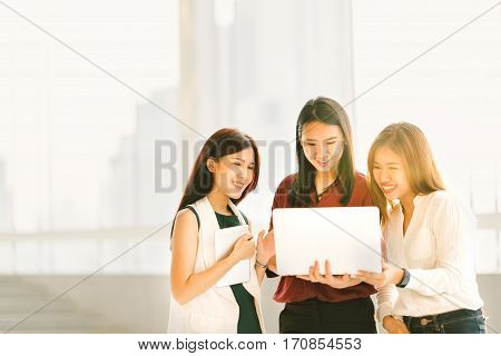 Three beautiful Asian girls on casual business meeting with laptop notebook and digital tablet at sunset modern lifestyle with gadget technology or working women concept with copy space