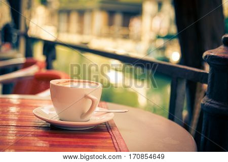 detail shot of a cup of cappucino on a table in a venetian cafe