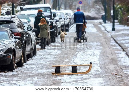 The Hague the Netherlands - February 12 2017: family walking on snow covered street sled in foreground