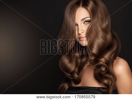 Brunette  girl with long  and   shiny wavy volume  hair .  Beautiful  model with curly hairstyle .
