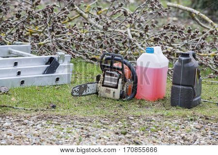 chainsaw and canister of gasoline and motor oil