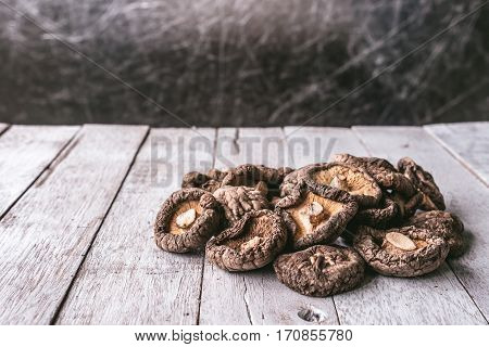 Dry Shiitake mushrooms on a wooden table.