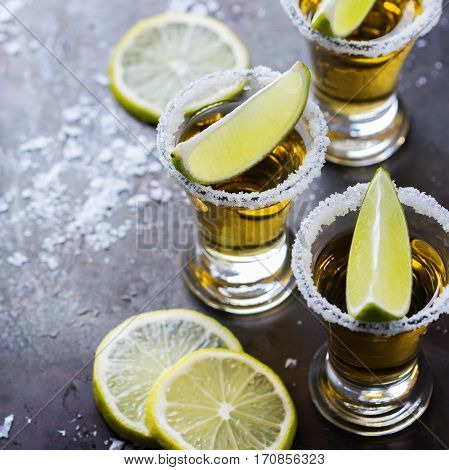 Alcohol, junk food, party, holidays concept. Golden mexican tequila shot on a grunge black table with salt and lime