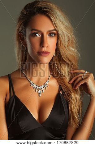 Suntanned girl portrait in a bra-top and necklace on gray background. She stands.