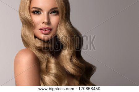 Blonde  girl with long  and   shiny wavy volume  hair .  Beautiful  model with curly hairstyle .
